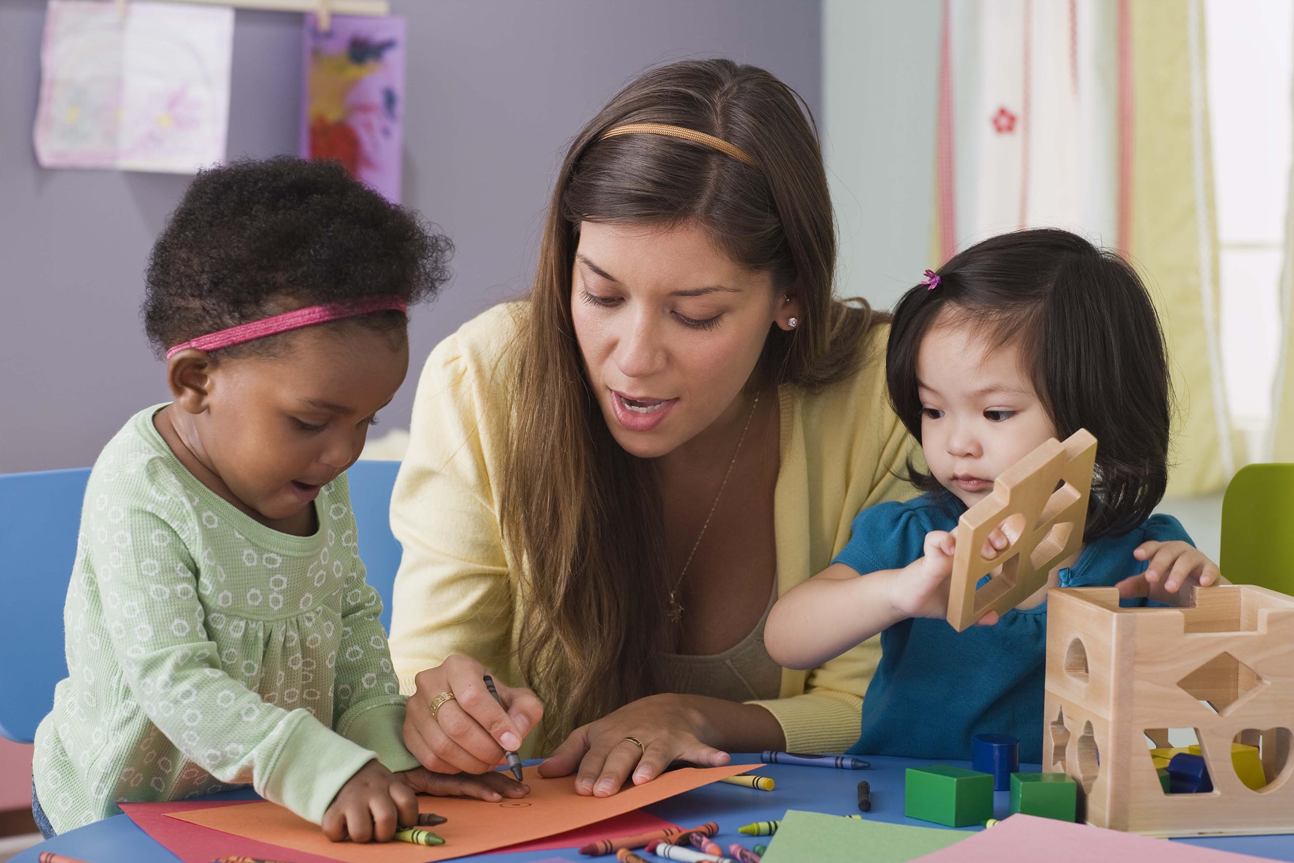 Photo of a teacher working with toddlers.